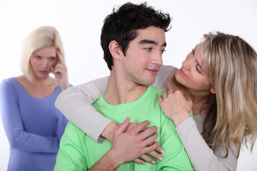 couple in love and jealous woman in background