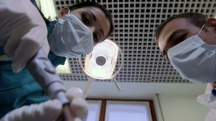 Dentist and assistant working in hospital, inspecting mouth