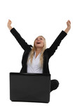 Triumphant businesswoman sitting at a laptop
