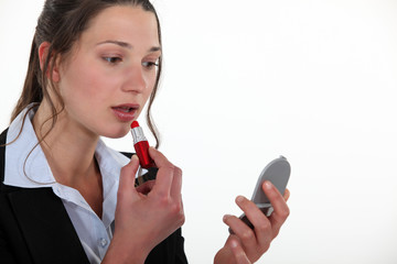 Woman putting lipstick on