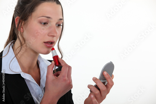 Woman putting lipstick on
