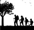 Hiking family with rucksacks in park in spring silhouette