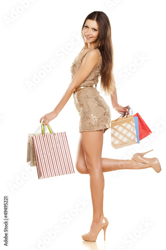 beautiful smiling brunette in a dress, holding a shopping bags