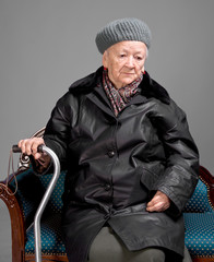 Old woman with a cane in winter outwear