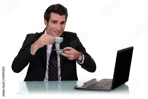 handsome businessman with laptop having cup of coffee