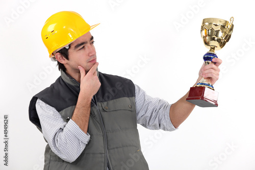 A construction worker holding a trophy.
