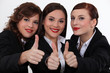 Three businesswomen giving the thumbs-up