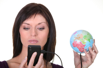 woman charging battery of cell phone with globe