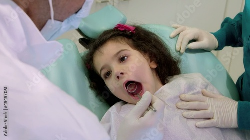 Dentist and assistant, checking teeth of young baby girl
