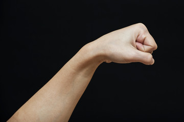 Female human fist isolated in a black background