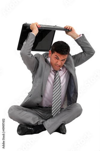 Businessman sat on the floor smashing laptop