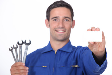 Mechanic holding selection of spanners and business card
