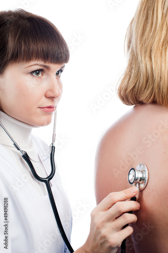 Doctor examining lungs of a female patient with stethoscope