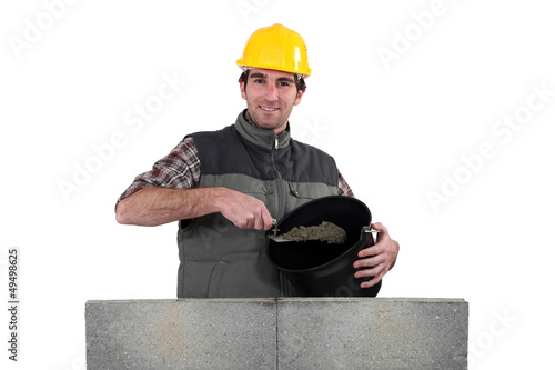 Bricklayer with a bucket of cement