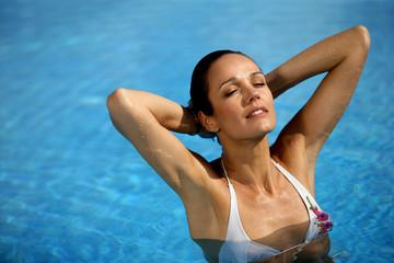 Brunette stood in pool wearing white bikini