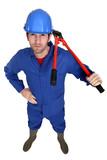 Man carrying bolt-cutter over shoulder