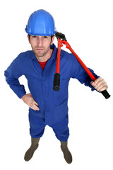 Man carrying bolt-cutter over shoulder