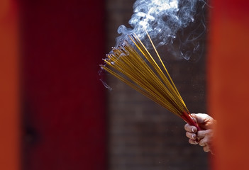 Hands Waving Smoking Incense Sticks at Temple