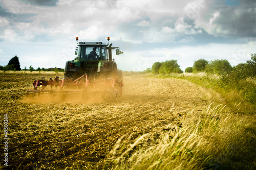 canvas print picture Tractor ploughs field