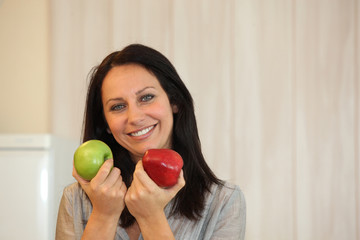 Woman choosing between red and green apples