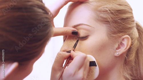 Make-up artist applying eyelash makeup to model's eye.