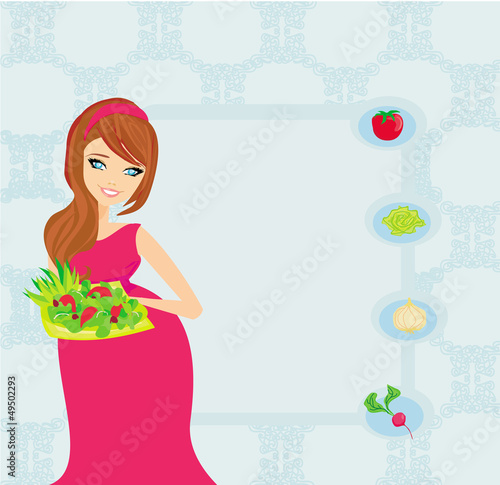 pregnant girl with a plate of salad in a hand.
