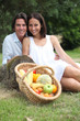 Couple sitting in the grass with fruit basket