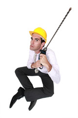 Businessman holding drill with long attachment