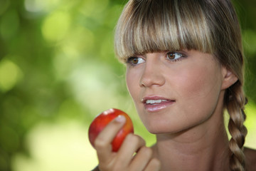 a blonde woman eating an apple