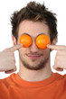 Man hiding his eyes with mandarins