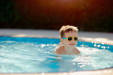 hot sunny day, the boy with sunglasses floating in the pool