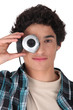 Young man hiding his eye with webcam