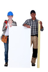 Construction workers holding white panel