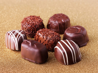 Assorted chocolate on golden background