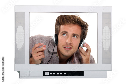 Young with headphones behind TV