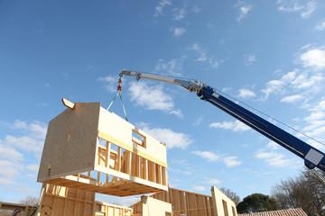 Crane lifting the framework of a house