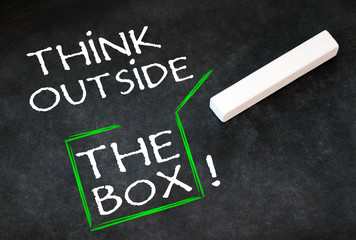 Think outside the box - Message on black chalkboard