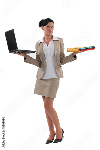 Woman holding laptop and documents