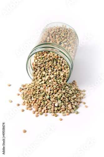 Dried lentil spilling from glass jar