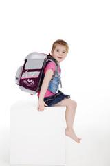 Junges Mädchen mit Schultasche sitzt und lacht