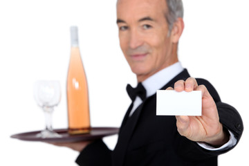waiter carrying bottle of wine and showing his personal card