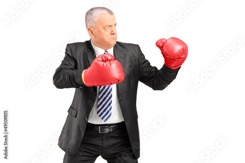 A mature businessman with red boxing gloves ready to fight