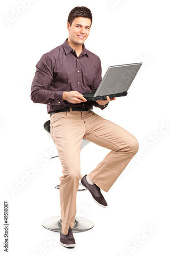 A smiling man sitiing on a high chair and working on a laptop