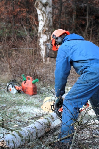 Man cutting wood with chainsaw, protective safety clothes