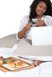 Woman having breakfast in bed and checking her emails