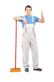 Full length portrait of a male cleaner with a broom giving thumb