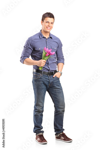 Full length portrait of a smiling guy holding flowers and lookin