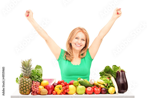 Happy woman with raised hands posing with pile of fruits and veg