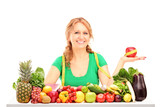 Smiling woman with fruits and vegetables holding an apple with m