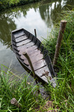 Partially submerged boat on shore in Marais Poitevin area